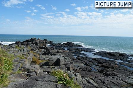 夏のウスタイベ千畳岩は緑と海と巨大なブロック状の岩とのコントラスト